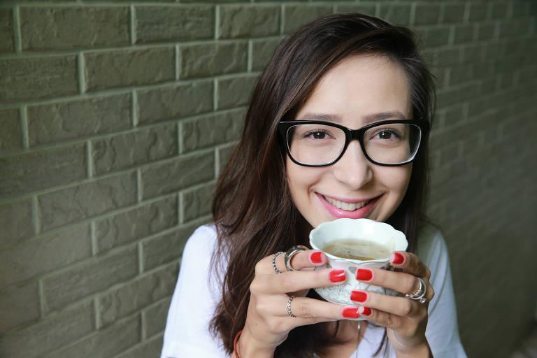 A advogada Thayla Pavani posa segurando uma xícara de chá