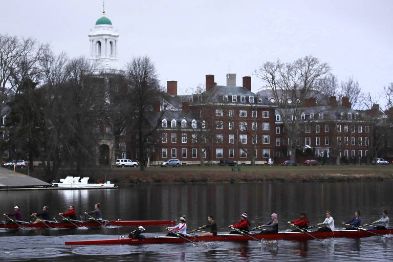 Os remadores estão em dois barcos vermelhos paralelos: um com cinco estudantes e outro com três. Campus é composto por prédios de tijolos vermelhos e janelas com bordas brancas. Do lado esquerdo, entre árvores sem folhas, aparece uma torre branca com cúpula verde.