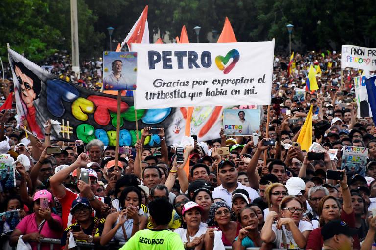 """Grupo de pessoas carrega bandeiras de partidos e faixas de apoio a Petro. Uma delas, em branco, diz: """"Petro, obrigado por expulsar a besta de Uribe que existia em mim""""."""