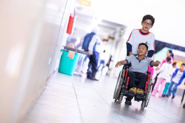 Micael dos Santos Lopes conduz o colega Kauã na cadeira de rodas