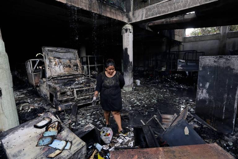 Mulher caminha por casa destruída por incêndio em Manágua, capital da Nicarágua