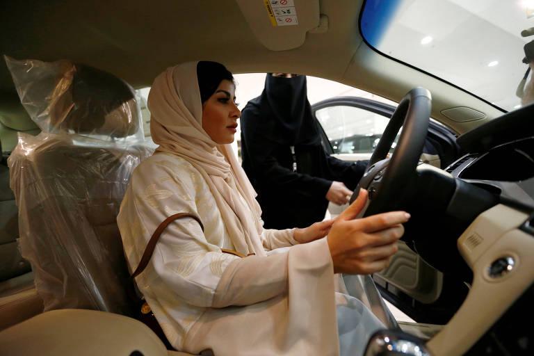 A cirurgiã saudita Fatima al-Nasseralah testa seu futuro carro numa concessionária de Riad, dias depois de o governo emitir sua carteira de motorista