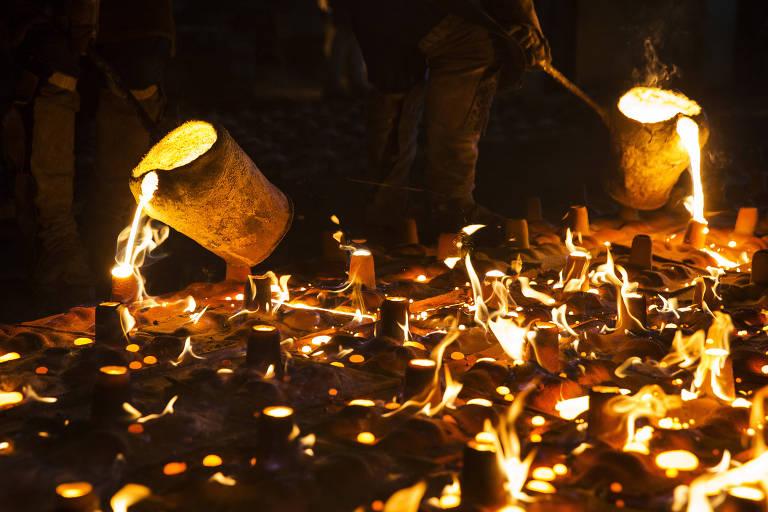 Operários especializados entornam ferro derretido em altíssima temperatura em moldes para fazer peças de freio para trens, em fábrica em Barueri (SP)