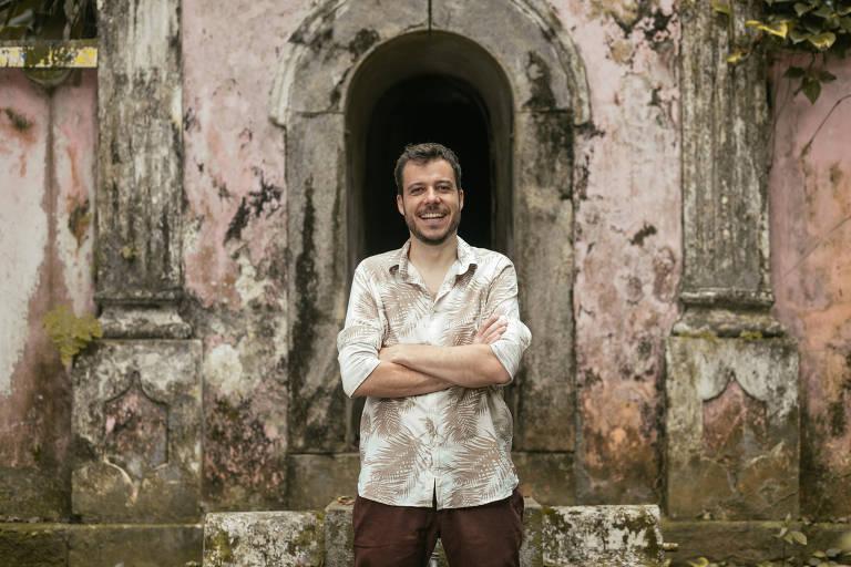O músico João Cavalcanti posa de pé, com os braços cruzados na altura do peito e sorrindo; ele é claro, tem cabelos curtos castanhos claros e usa barba. Veste uma camisa estampada com folhas beges em fundo branco e posa diante de um edifício rosado, em ruínas