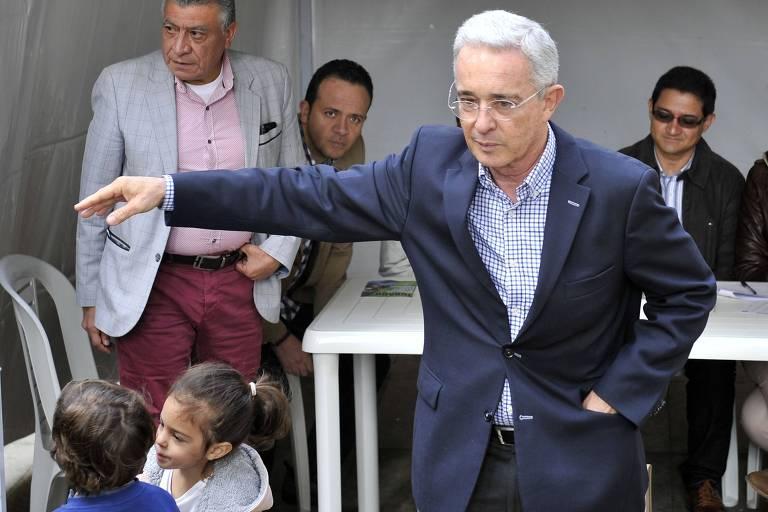O ex-presidente da Colômbia Álvaro Uribe vota com seus netos na capital do país; ele é considerado o principal cabo eleitoral do vencedor Duque