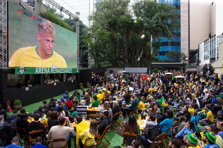 Sentado em cadeiras, publico assiste ao jogo do Brasil no telão, que foca rosto de Neymar