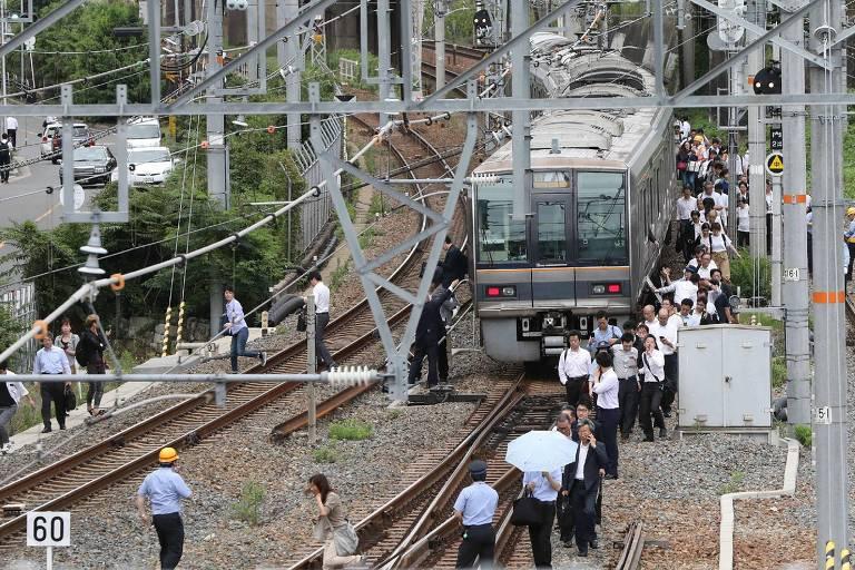 Passageiros de um trem em Osaka, no Japão, deixam os vagões e andam pelos trilhos depois de terremoto interromper funcionamento da linha