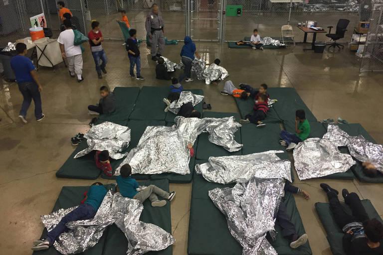 Crianças que foram separadas dos pais se acomodam em esteiras dentro de um centro de detenção da polícia de fronteira dos EUA, em Rio Grande, no Texas