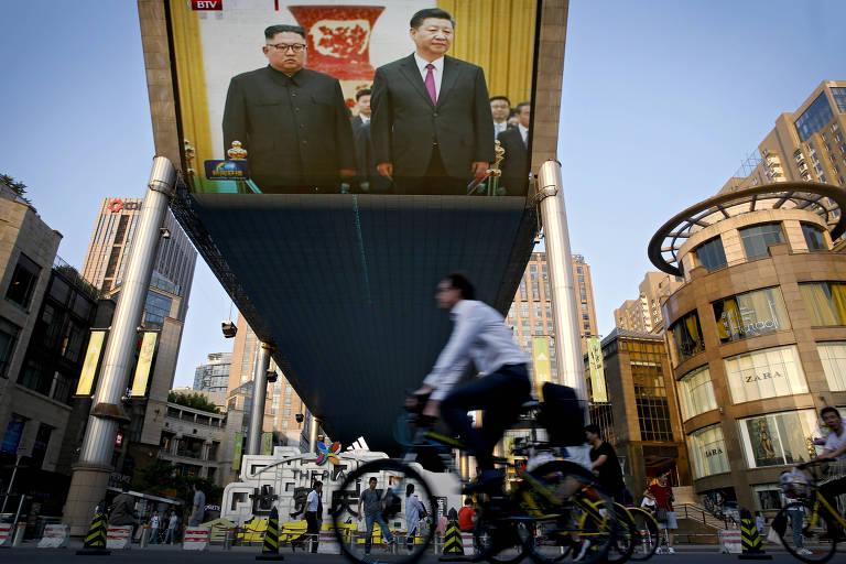 Telão em Pequim exibe o encontro entre o ditador norte-coreano Kim Jong-un e o líder chinês Xi Jinping