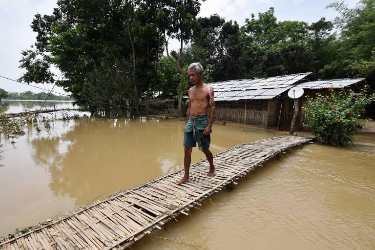 Homem caminha em vila alagada no estado de Assam, na Índia, um dos mais atingidos pela chuva