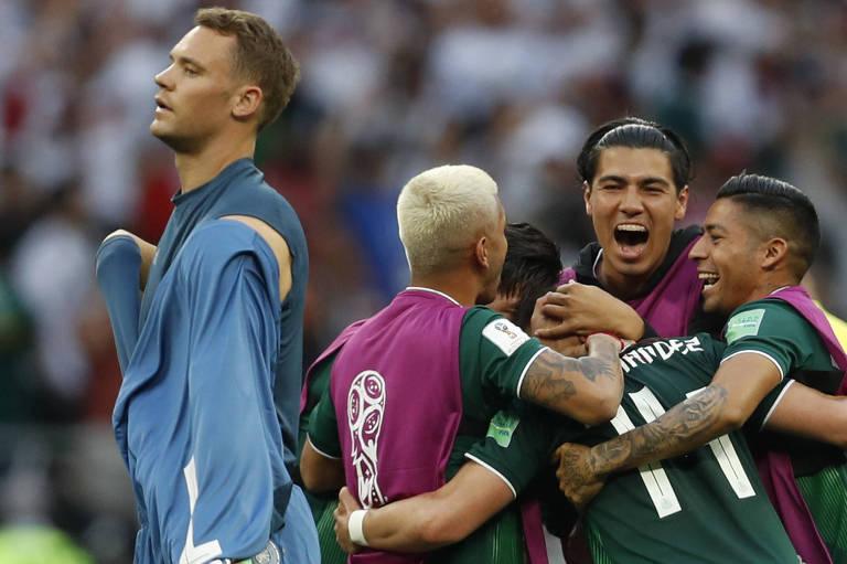 O goleiro da Alemanha, Manuel Neuer, deixa o campo enquanto jogadores mexicanos comemoram vitória