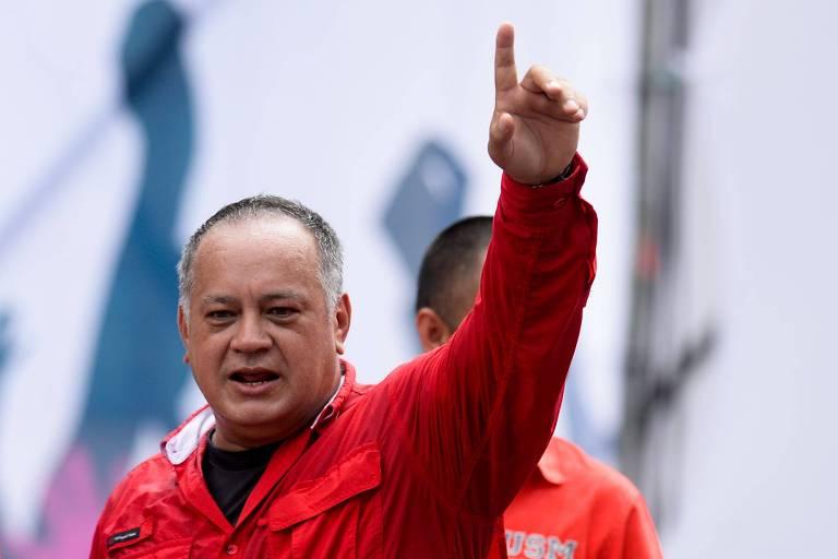 De camisa vermelha e camiseta preta por baixo, Diosdado Cabello levanta a mão esquerda com o dedo indicador em riste