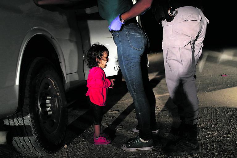 Mennina hondurenha de dois anos chora enquanto sua mãe é revistada detida por agentes de fronteira perto de McAllen, no Texas