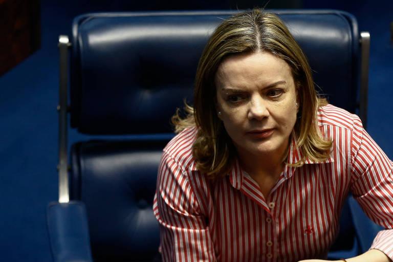 A senadora Gleisi Hoffmann (PT-PR) está sentada em sua cadeira no plenário do Senado federal, apoiando o cotovelo esquerdo sobre a mesa e vestindo uma camisa de listras vermelhas.
