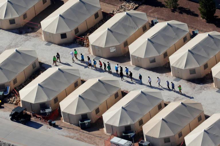 Um grupo de dez crianças aparece perfilado em um corredor formado por cinco tendas de cor bege de um lado e cinco tendas da mesma cor do outro. Ao lado delas há dois agentes de imigração.