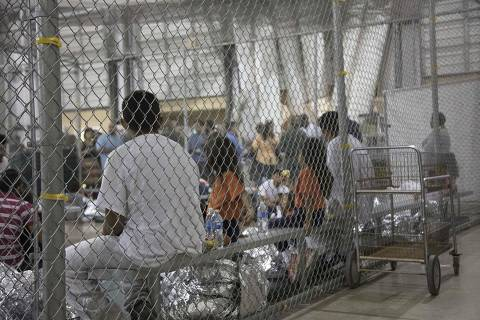 TOPSHOT - CORRECTION - This US Customs and Border Protection photo dated June 17, 2018 obtained June 18, 2018 shows intake of illegal border crossers by US Border Patrol agents at the Central Processing Center in McAllen, Texas. Children have been taken away from their mothers and fathers in the Border Patrol's South Texas Rio Grande Valley sector, with many brought to the Central Processing Station in McAllen, Texas, since the policy was announced on May 7, according to Manuel Padilla, the Border Patrol sector chief. / AFP PHOTO / US Customs and Border Protection / Handout / RESTRICTED TO EDITORIAL USE - MANDATORY CREDIT