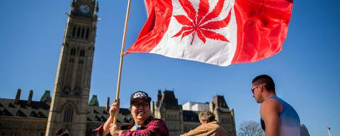 (FILES) In this file photo taken on April 20, 2016 showing a woman waving a flag with a marijuana leef on it next to a group gathered to celebrate National Marijuana Day on Parliament Hill in Ottawa, Canada.