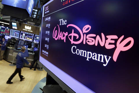 FILE - In this Aug. 8, 2017, file photo, The Walt Disney Co. logo appears on a screen above the floor of the New York Stock Exchange. Disney is making a $70.3 billion counter bid for Fox?s entertainment businesses following Comcast?s $65 billion offer for the company. (AP Photo/Richard Drew, File) ORG XMIT: NYAG302