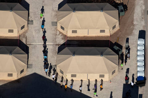 Immigrant children are led by staff in single file between tents at a detention facility next to the Mexican border in Tornillo, Texas, U.S., June 18, 2018. Picture taken June 18, 2018  REUTERS/Mike Blake ORG XMIT: AAL301
