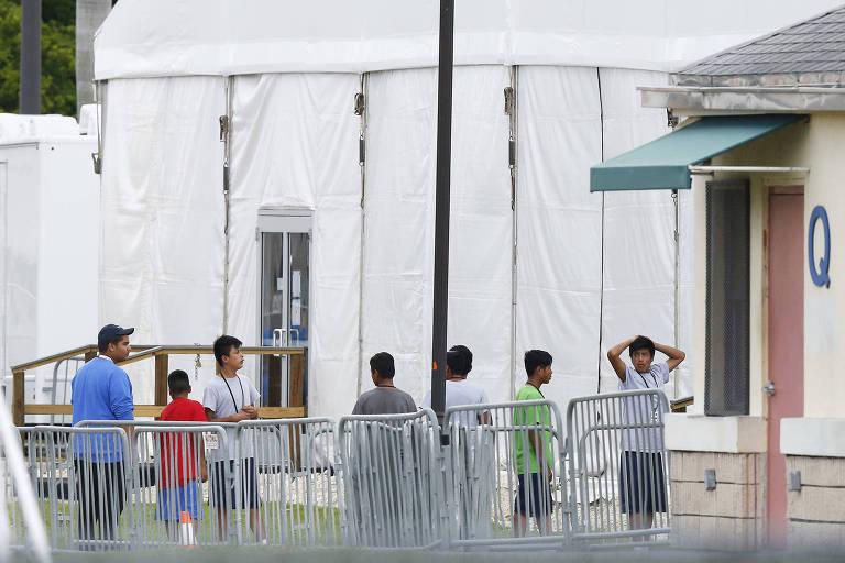 Filhos de imigrantes que tentaram entrar ilegalmente nos EUA caminham em frente a abrigo para menores em Homestead (Flórida), na quarta (20)