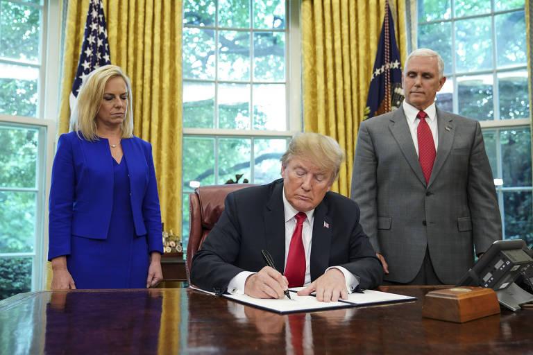 Donald Trump (centro) assina decreto acompanhado da secretária de Segurança Doméstica, Kirstjen Nielsen (à esquerda), e do vice-presidente Mike Pence