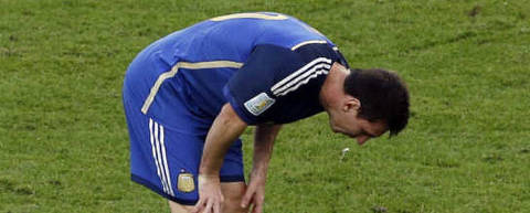 Argentina's Lionel Messi vomits as Germany's Mats Hummels walks by during the World Cup final soccer match between Germany and Argentina at the Maracana Stadium in Rio de Janeiro, Brazil, Sunday, July 13, 2014. (AP Photo/Themba Hadebe)