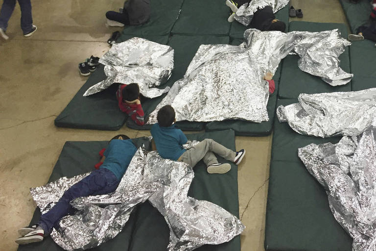 Crianças estão sentadas e deitadas em seis colchonetes verdes, algumas delas cobertas com uma manta prateada.