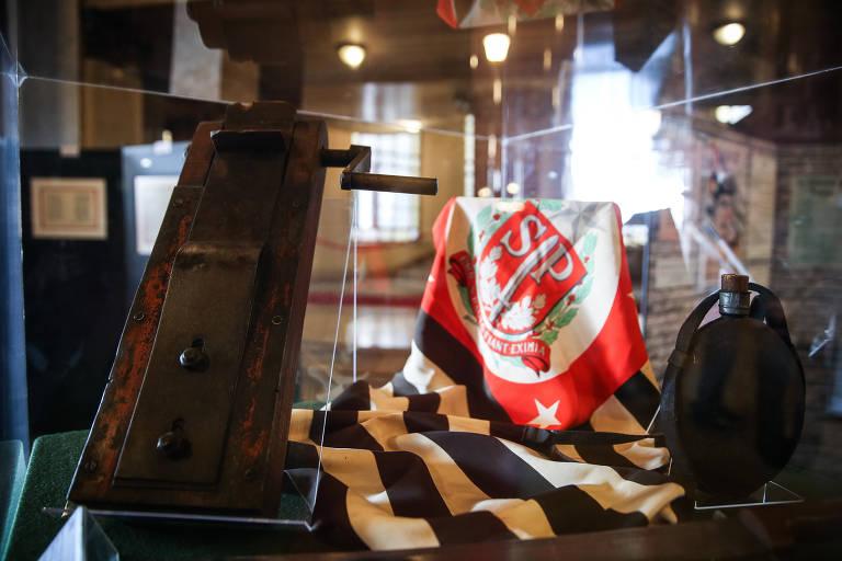"""Matraca original e bandeira com o brasão de armas de São Paulo, adotado em agosto de 1932, com a inscrição """"Pro São Paulo fiant eximia"""""""