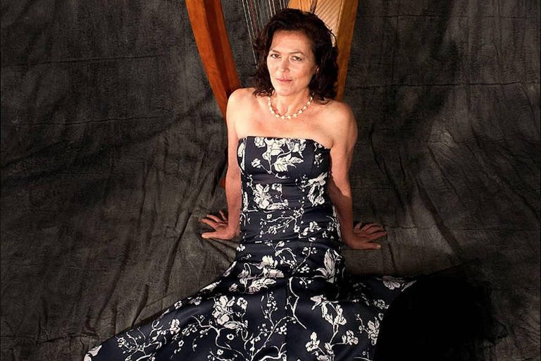 Zoe Vandermeer posa para foto sentada em frente a uma harpa