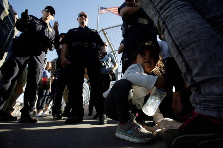 De camiseta branca e calça jeans, menina segura garrafa d'água ao lado da perna de um adulto que está em uma fila. À direita há dois agentes de imigração vestidos de preto, que são vistos de baixo para cima. Ao fundo, no alto, uma bandeira pequena dos EUA tremula em uma grade.
