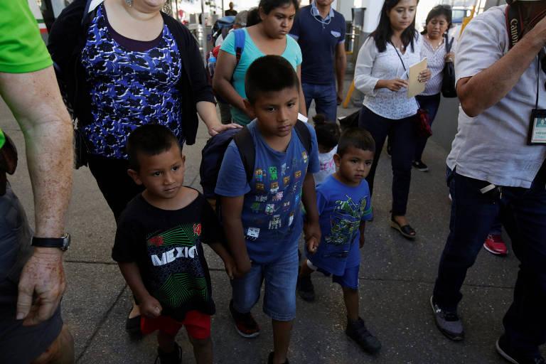 """Três meninos aparecem à frente da imagem. O à esquerda usa camiseta preta grande, com a palavra """"México"""" e detalhes em vermelho e verde. O ao centro usa bermuda jeans, camiseta azul estampada e uma mochila nas costas. E o à direita está de short e camiseta azul. Os três andam de mãos dadas, à frente de duas mulheres que os levam atrás, uma de calça preta, casaco preto e blusa azul e outra, de blusa verde água. Eles estão em meio a outras pessoas que também se aproximam da fila."""