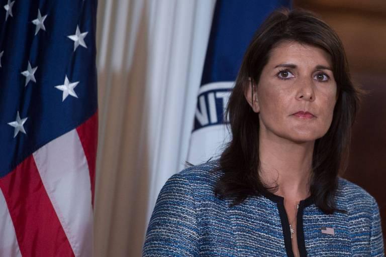 Haley aparece à frente das bandeiras dos EUA (à esquerda) e da representação americana na ONU (à direita). Ela usa um blazer azul jeans com contornos pretos e tem uma bandeira dos EUA na lapela.
