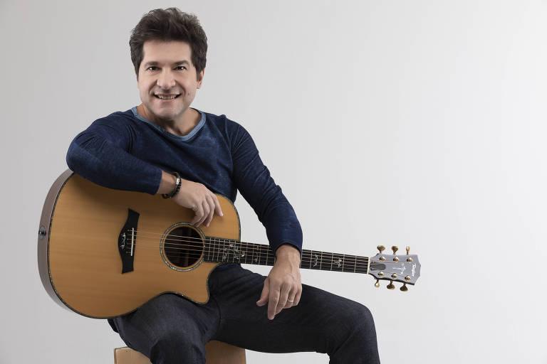 Cantor Daniel, sentado em um banco, com um violão no colo