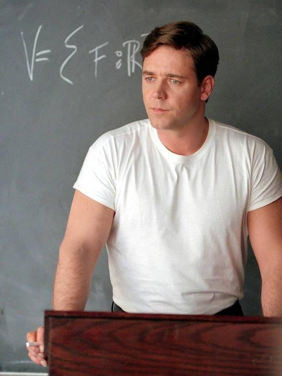 """O ator Russell Crowe interpreta John Nash (matemático que tinha esquizofrenia), em cena do filme """"Uma Mente Brilhante""""; atrás do ator, em um quadro negro, há uma equação matemática; ele está apoiado em um púlpito, com um giz entre os dedos"""