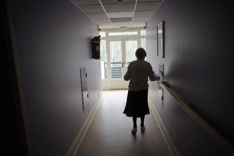 Mulher com alzheimer anda por corredor escuro
