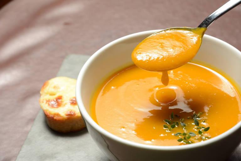 Foto mostra uma cumbuca branca cheia de sopa de abóbora. Uma colher tira um pouco da sopa.