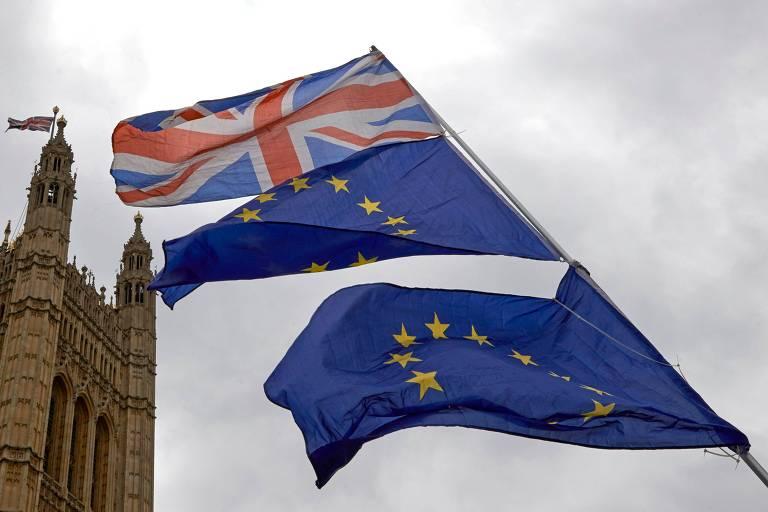 Duas bandeiras da União Europeia e uma do Reino Unido no topo tremulam ao lado de uma das torres do prédio do Parlamento britânico, que vista à esquerda