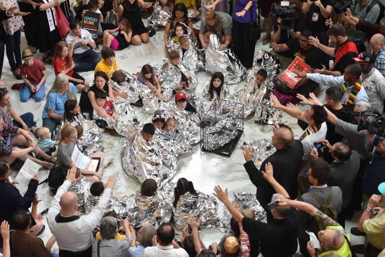 Grupo de pessoas faz uma roda e levanta as mãos como se estivessem em oração. No meio deles, há crianças usando cobertores prateados e uma gaiola.