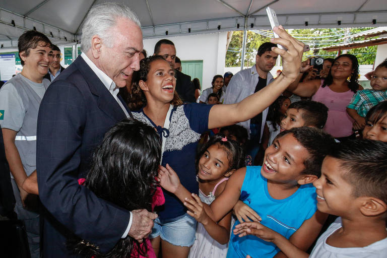 Temer está cercado por cinco crianças. Ele abraça uma menina, de camisa vermelha, enquanto uma menina e outros dois meninos se aproximam à direita, sorridentes. Uma adolescente, mais velha, arma uma selfie  com o presidente. A cena é observada por um grupo de adultos, que aparece atrás, dentro de uma área coberta.