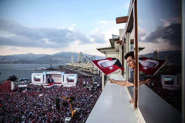 Mulher acena com bandeira turca da janela de um apartamento, enquanto embaixo milhares de pessoas vestindo vermelho, uma das cores da bandeira, esperam o candidato Ince, que falaria em um palco branco montado no centro de uma praia. Ao fundo à esquerda é possível ver o mar Mediterrâneo.