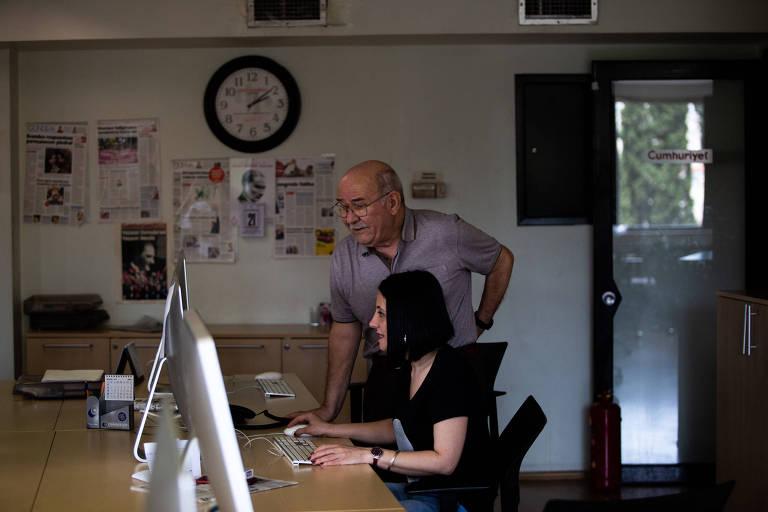 Engin fica de pé ao lado de Unay, sentada em frente a um computador. Os dois estão em uma sala com uma mesa de madeira comprida. Ao fundo, um relógio de parede de borda preta e fundo branco e capas de jornal coladas na parede.