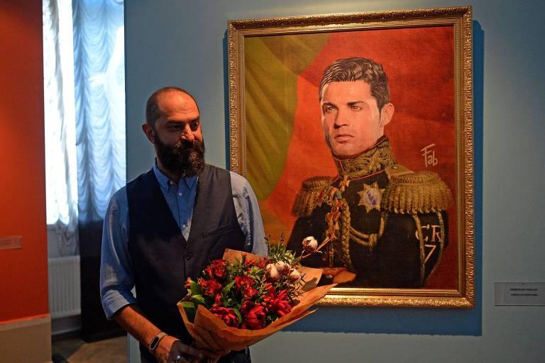 O artista italiano Fabrizio Birimbelli ao lado do retrato de Cristiano Ronaldo na mostra 'Like the Gods'