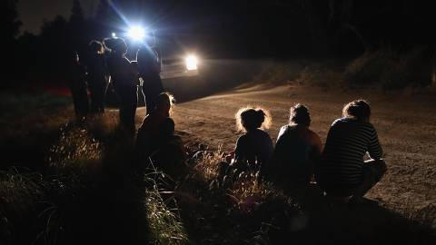 MCALLEN, TX - JUNE 12: A U.S. Border Patrol vehicle illuminates a group of Central American asylum seekers before taking them into custody near the U.S.-Mexico border on June 12, 2018 in McAllen, Texas. The group of women and children had rafted across the Rio Grande from Mexico and were detained by U.S. Border Patrol agents before being sent to a processing center for possible separation. Customs and Border Protection (CBP) is executing the Trump administration's zero tolerance policy towards undocumented immigrants. U.S. Attorney General Jeff Sessions also said that domestic and gang violence in immigrants' country of origin would no longer qualify them for political asylum status.   John Moore/Getty Images/AFP == FOR NEWSPAPERS, INTERNET, TELCOS & TELEVISION USE ONLY ==