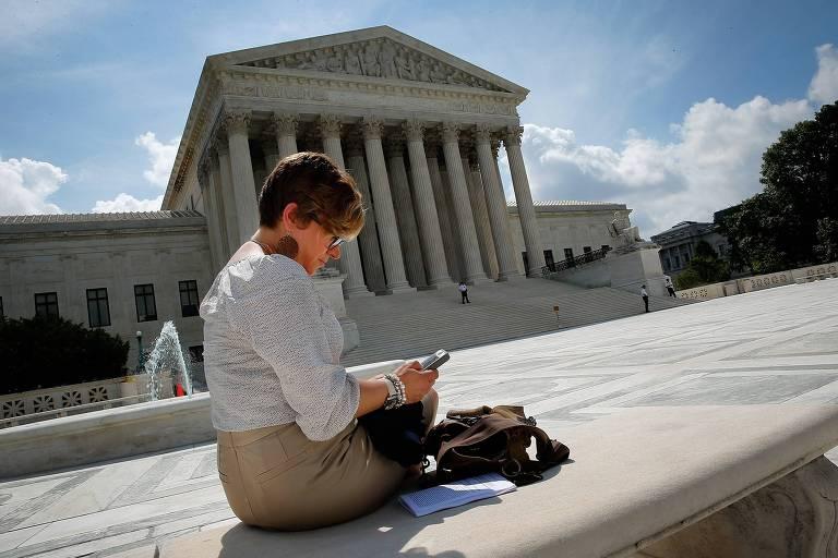 Mulher usa celular na frente da Suprema Corte, em Washington; tribunal decidiu que a polícia precisa obter um mandado para rastrear usuários por meio dos dados de localização do aparelho