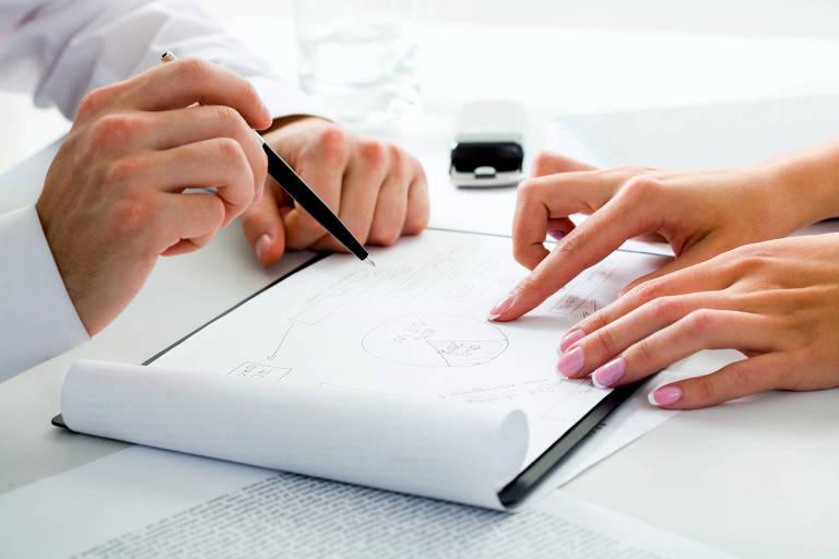 Quatro mãos ao lado de uma folha em branco, escrevendo
