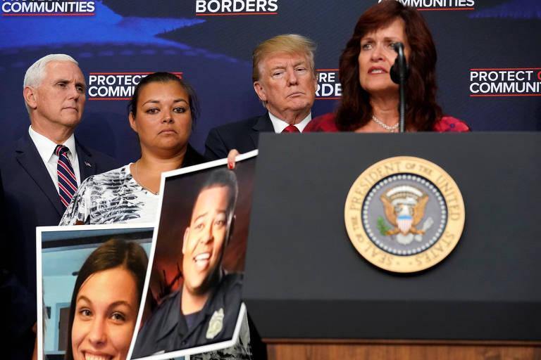 Trump e Pence aparecem por trás de duas mães que carregam fotos das vítimas. Uma delas, de camisa vermelha, está no púlpito do presidente discursando. A outra, de branco, está entre Trump e Pence.