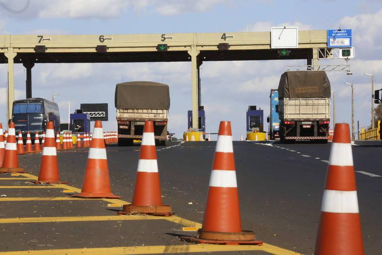A foto mostra um pedágio no meio da estrada. Alguns cones estão enfileirados na frente, indicando o caminho para os motoristas