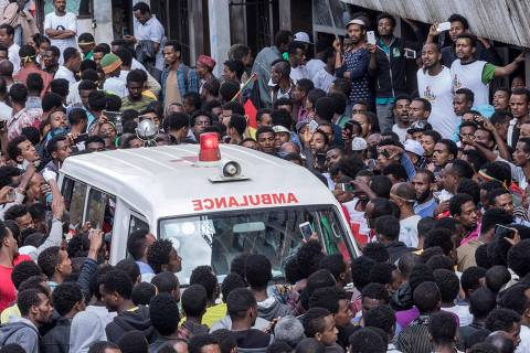 Ethiopians gather around an ambulance in Meskel Square in Addis Ababa on June 23, 2018, after an attack on a rally called by the Prime Minister Abiy Ahmed. The organiser of a pro-government rally in Ethiopia that was hit by a grenade blast said the attacker had aimed for Prime Minister Abiy Ahmed but was stopped by police. The attack injured 83 people, according to an aide to the prime minister, and marred an event aimed at building support for Abiy, who has pushed an aggressive reform agenda since taking office in April. / AFP PHOTO / YONAS TADESE