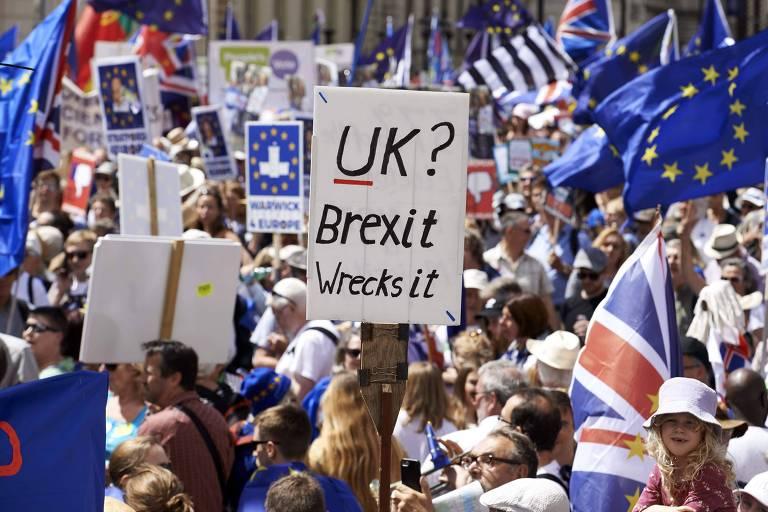 """Grupo de manifestantes, com centenas de pessoas, aparece na foto do alto com várias bandeiras da União Europeia e cartazes. O que está à frente traz a mensagem """"Reino Unido? O brexit destrói isso"""""""