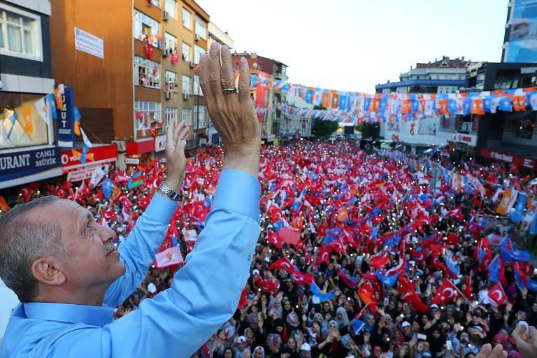 De camisa azul clara, Erdogan levanta as mãos para o céu. Abaixo do palco onde ele está há milhares de apoiadores em uma rua de sobrados com bandeiras da Turquia e azuis de sua campanha.